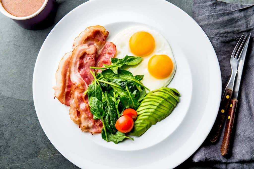 Ketogenic diet breakfast with fried egg, bacon and avocado, spinach and bulletproof coffee - is a high fat keto diet healthy