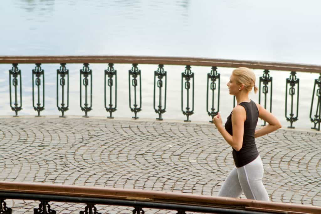 A young woman running on bridge in urban environment - post on Is it Bad to Do Abs Everyday
