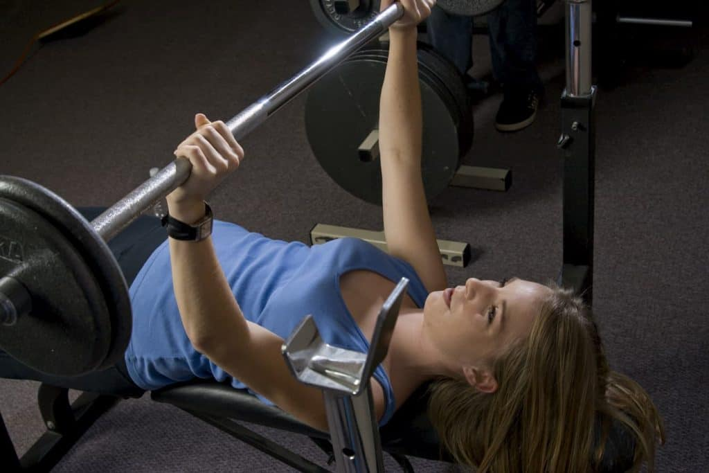Beautiful young blond woman doing bench presses with weights in a fitness location - post on chest and back same day