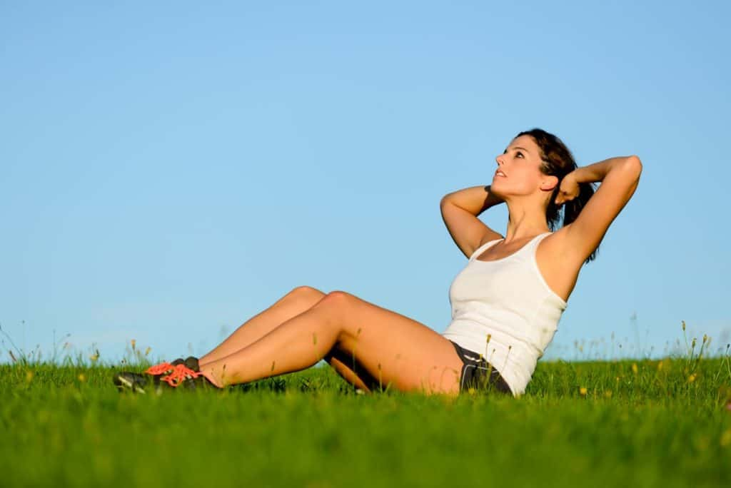 Woman doing an outdoor set of fitness crunches workout - post on Is it Bad to Do Abs Everyday