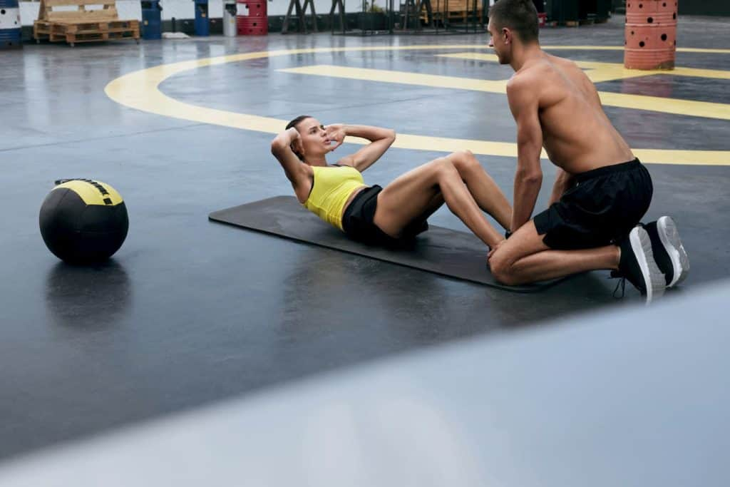 Woman doing sit-ups while her male trainer holds her feet - post on Is it Bad to Do Abs Everyday