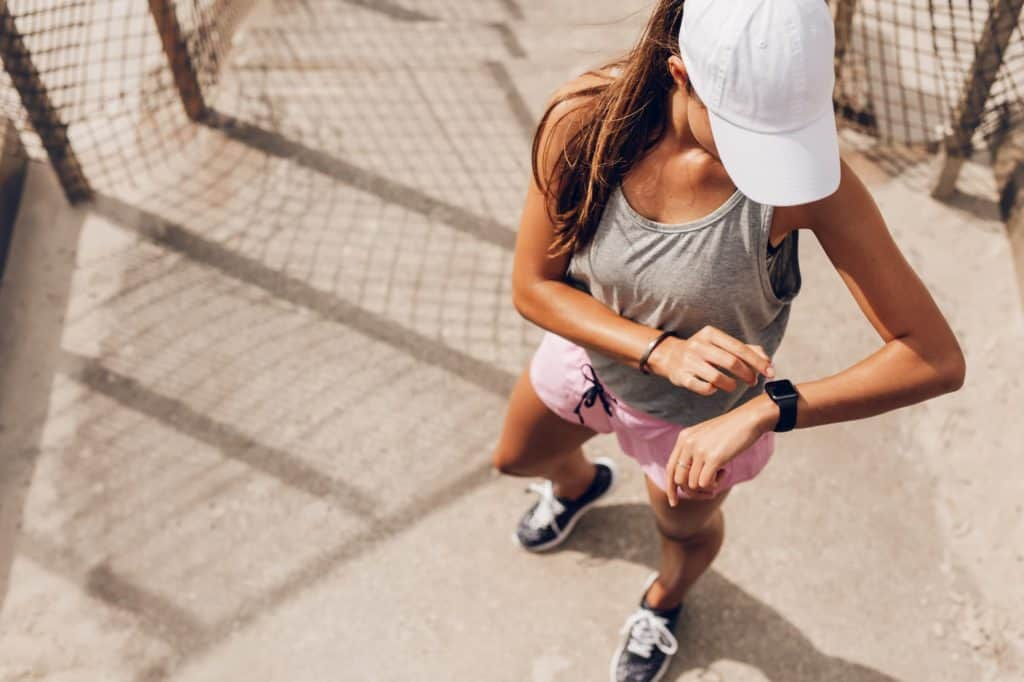 Female runner looking at smart watch heart rate monitor - post on How To Lower Resting Heart Rate