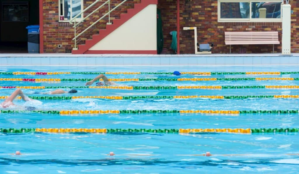 Four people swimming laps at an outdoor pool - How Long Do You Need to Swim to Get a Good Workout