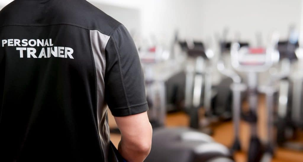 Personal trainer in the gym working with clients - Pros And Cons Of Being A Personal Trainer