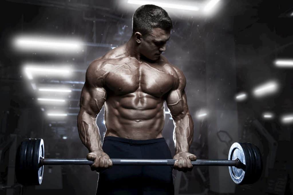 athletic muscular bodybuilder workout with barbell - post on how long does a pump last