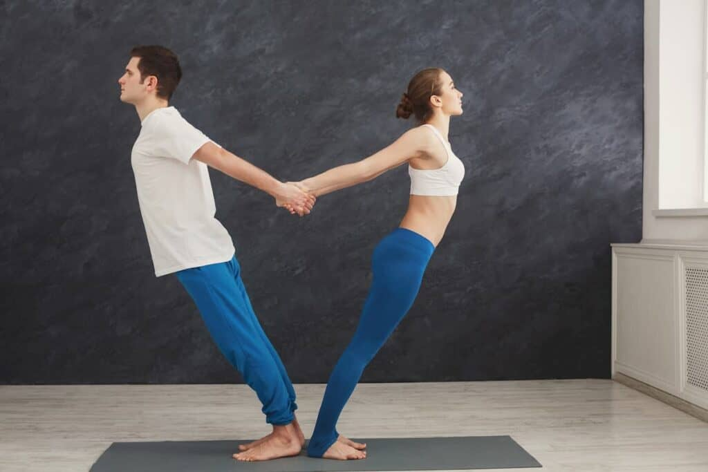 Couple training yoga in balance pose - what are the components of physical fitness