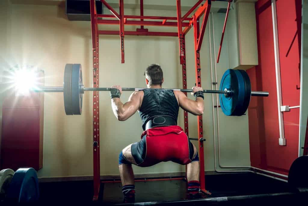 Young teenage man doing squats in indoor gym club - Is Running After Leg Day A Good Idea