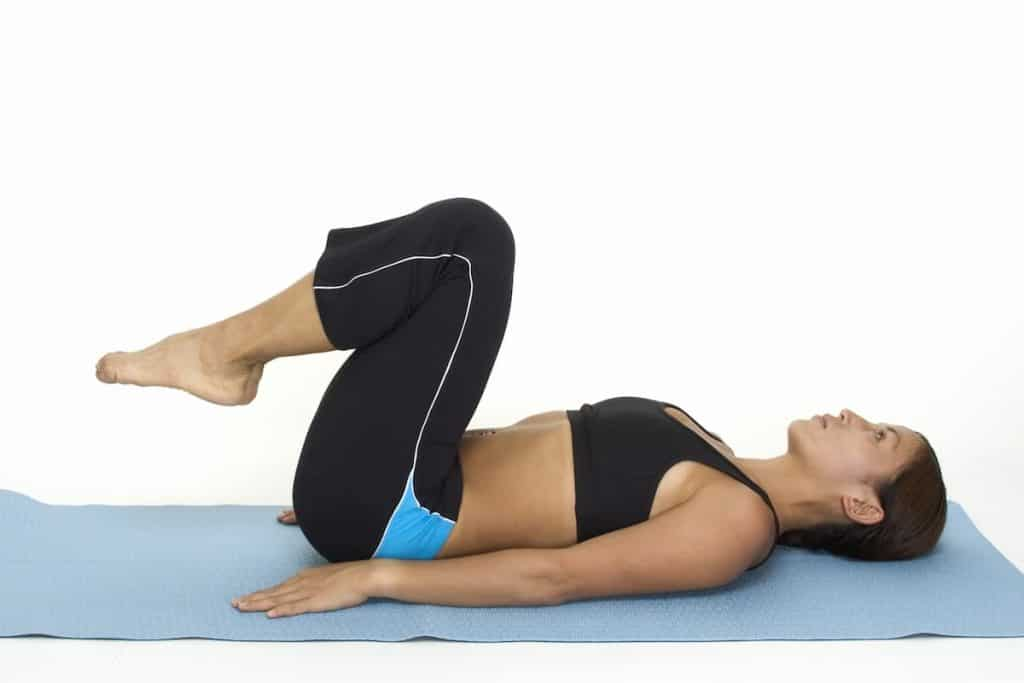 A female fitness instructor demonstrates the starting position of the reverse crunch - What Is A Reverse Crunch
