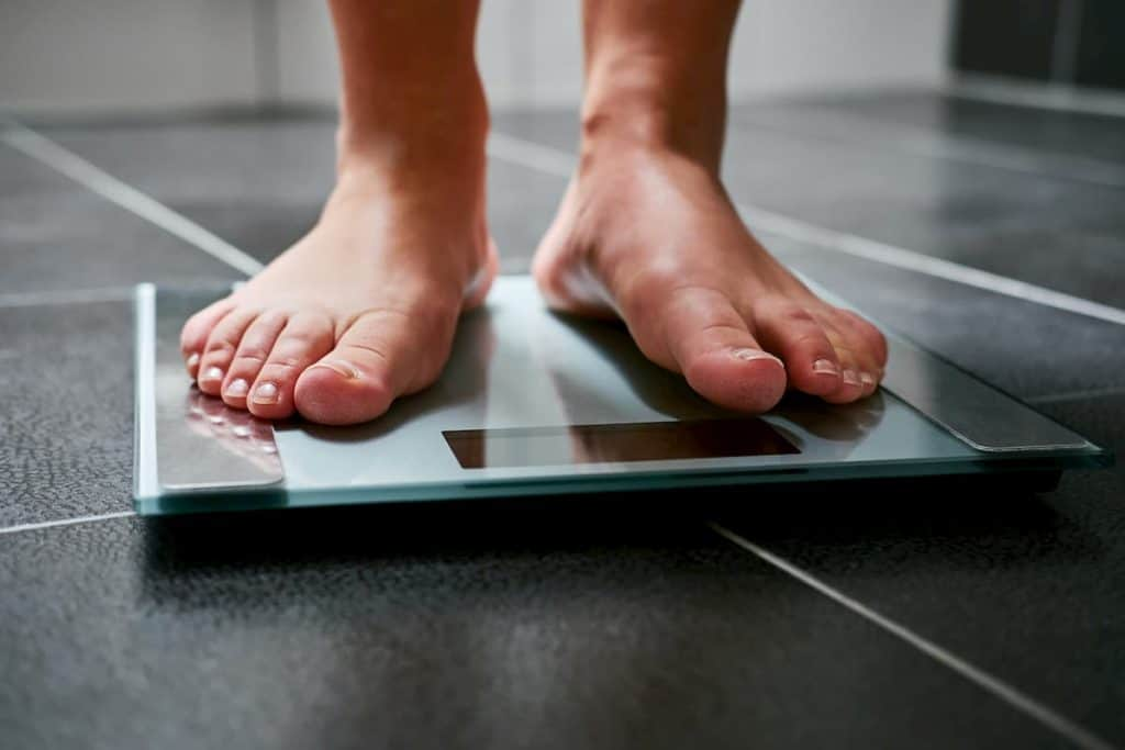 feet with weight scale in the bathroom - Do Calories Matter on Keto or Just Carbs
