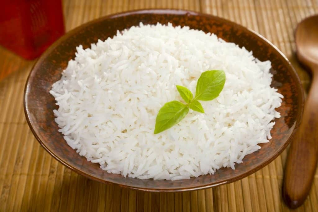 A bowl of perfectly cooked, plain Basmati rice, in an Asian style bowl, with a garnish of Thai Basil. - Is Basmati Rice Healthy For Weight Loss