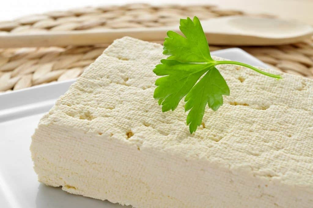 Closeup of a block of tofu in a plate - Living While On A Vegan Ketogenic Diet