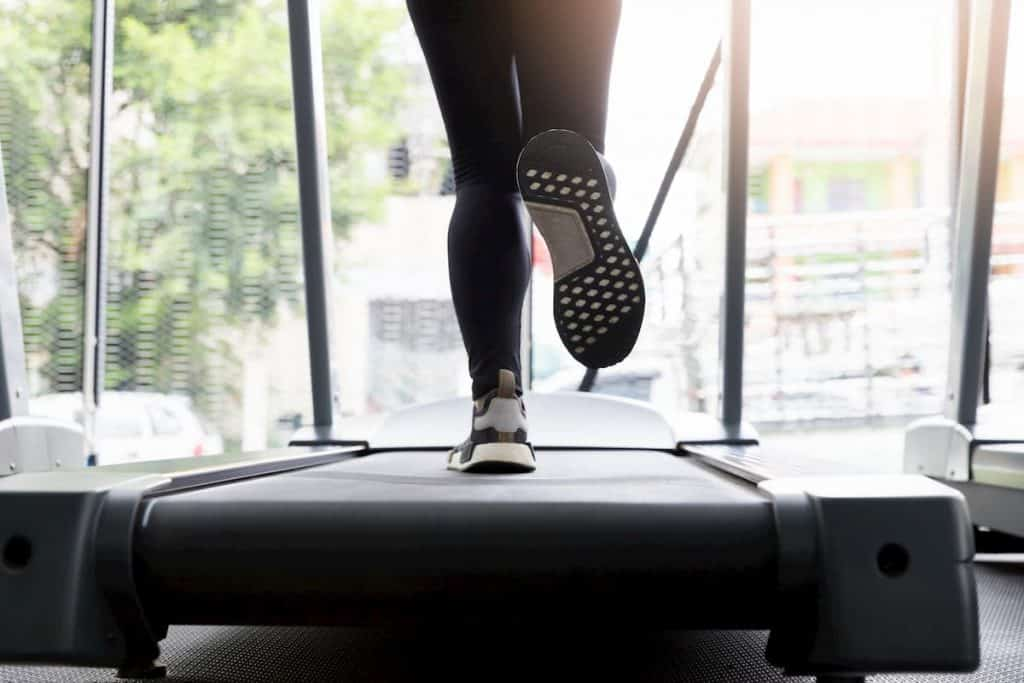 Woman on a treadmill in a fitness club - What Workouts Burn the Most Fat