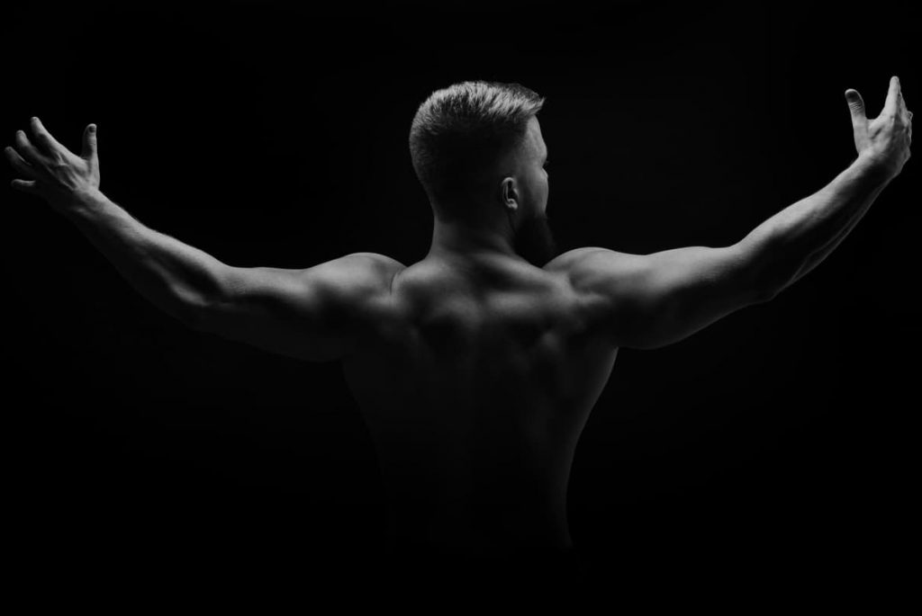 Muscular man stands with his back and spread his arms to the side - what is considered broad shoulders