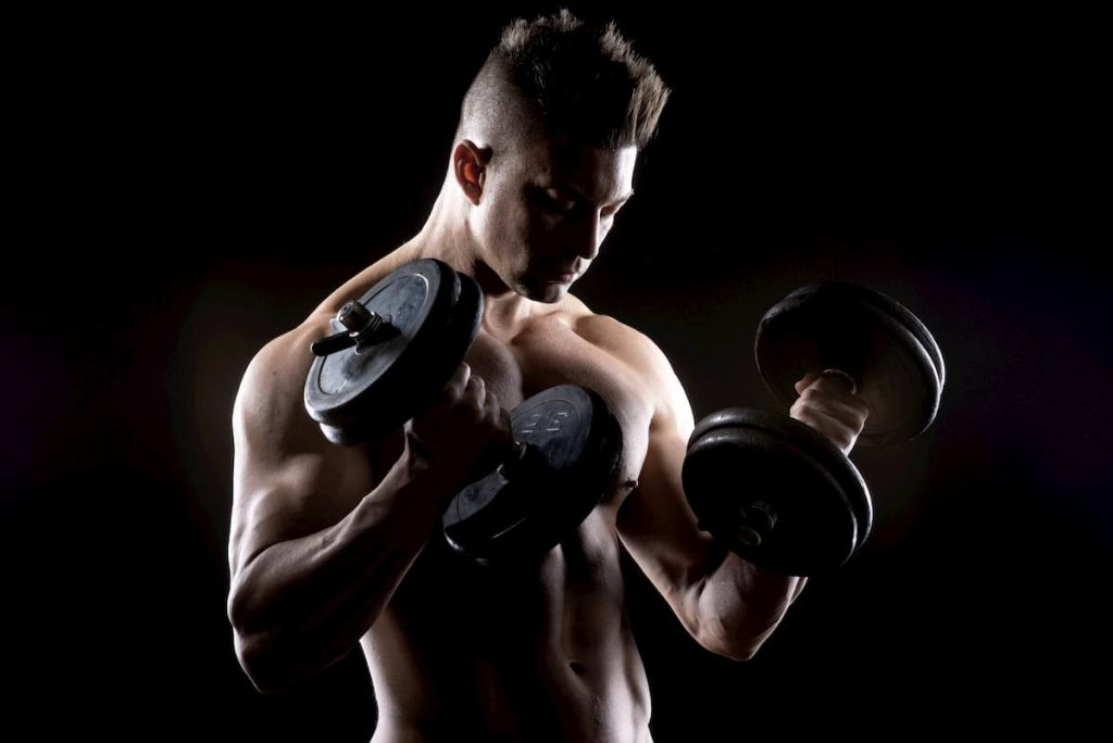 Muscular man weightlifting - is calisthenics better than weightlifting