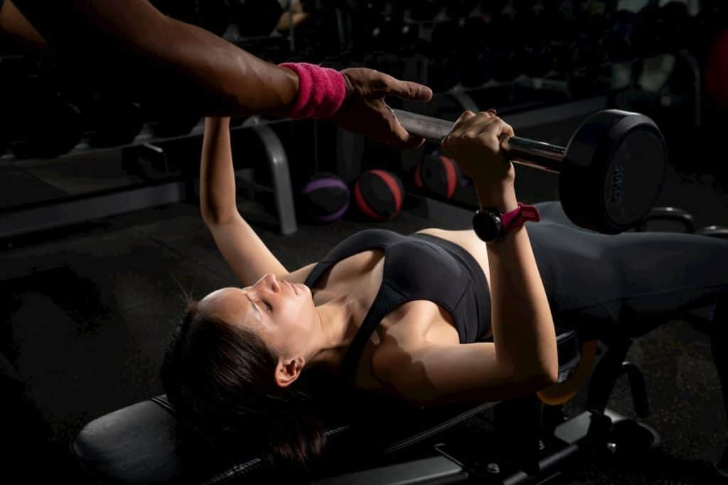 Personal trainer helping woman bench press in gym - How to Bench Without a Spotter