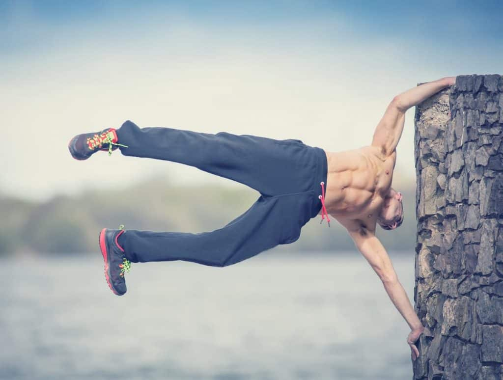 Urban fitness workout calisthenics, male in flag pose on wall over water - is calisthenics better than weightlifting