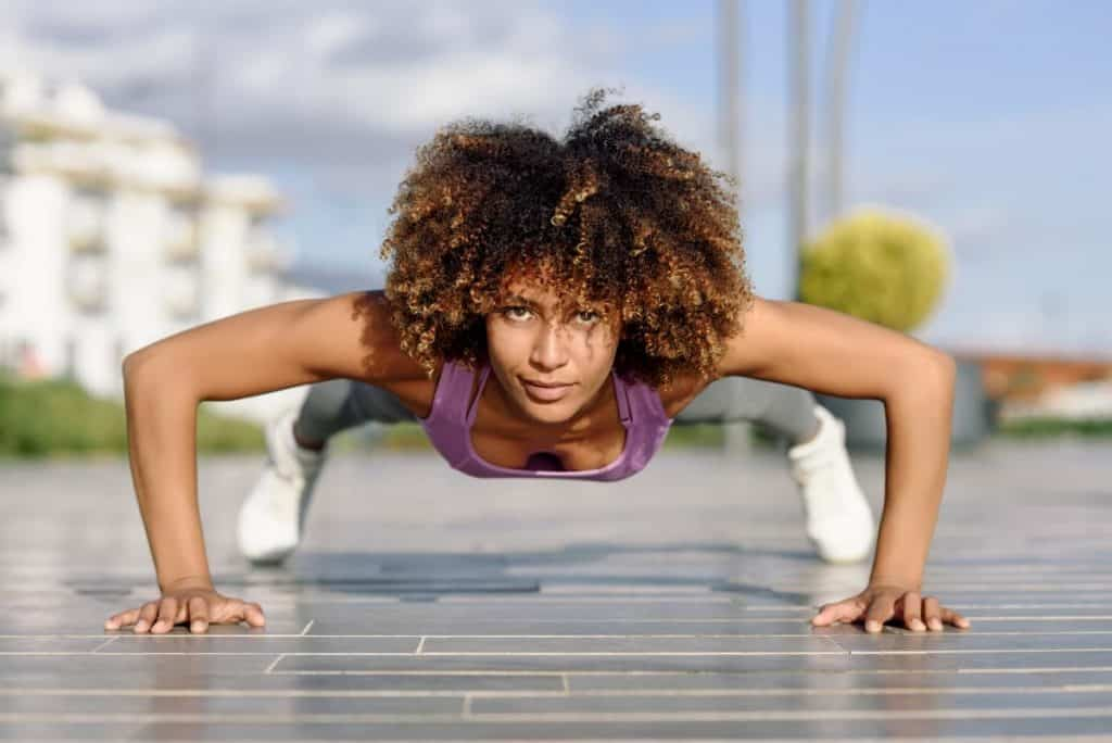 Fit woman doing pushups on brick - Do Push Ups Help Build Muscle