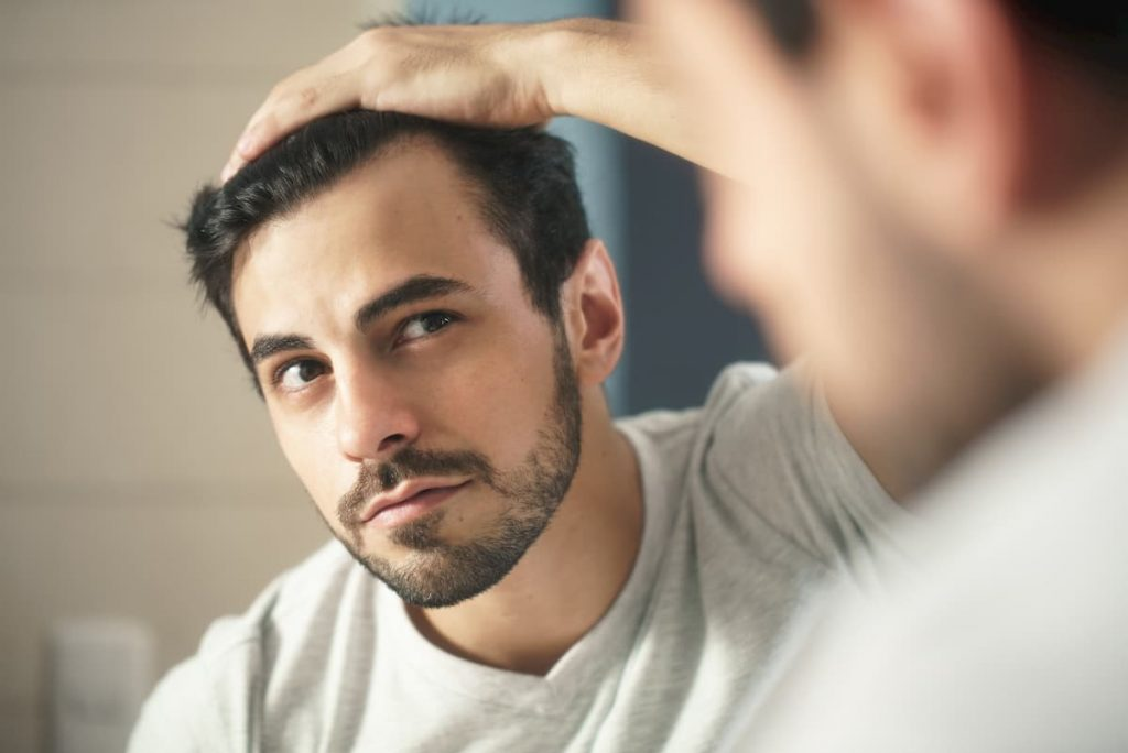 man worried for hair loss and looking at mirror his receding hairline - hair loss on keto diet
