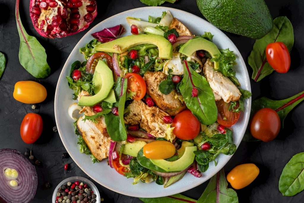 common keto mistakes - Healthy salad with grilled chicken breast, avocado, pomegranate seeds and tomato