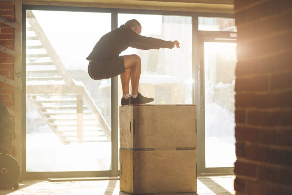 determined sportsman performing plyometric box jumps indoor, in crossfit functional workout