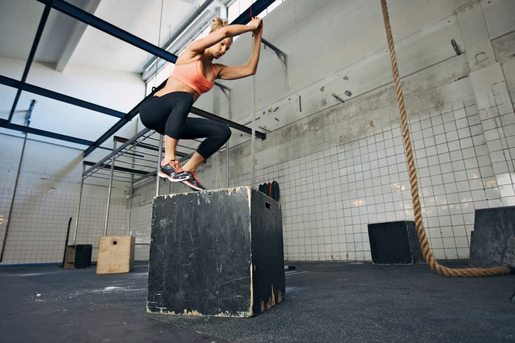 Fit young woman box jumping at a crossfit style gym