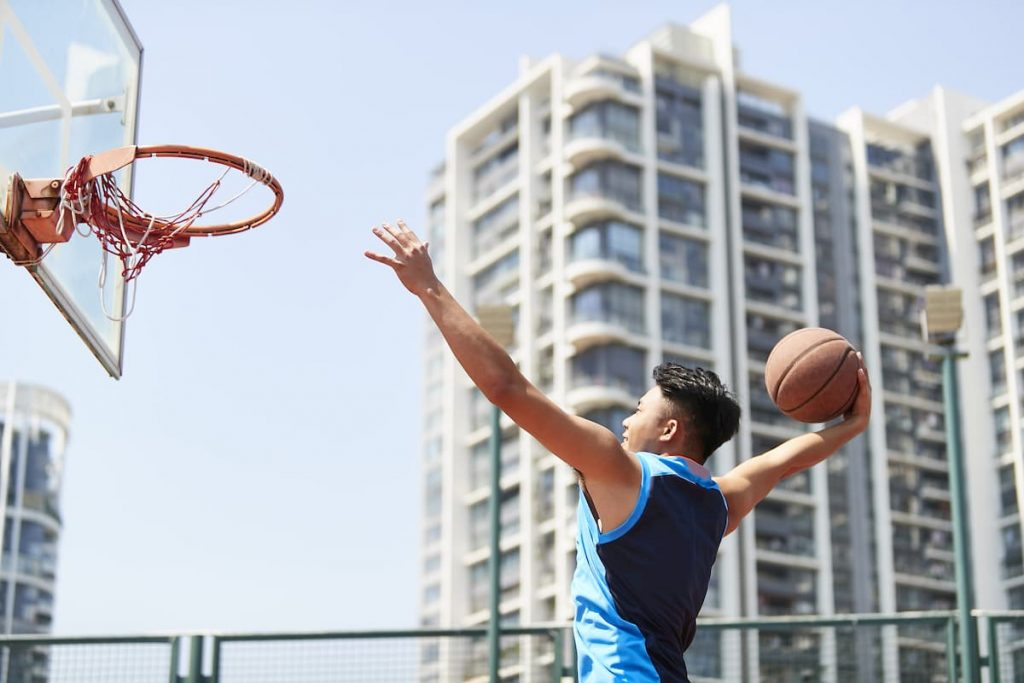Young asian adult man dunking basketball on outdoor court against city background