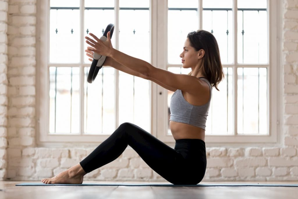 Sporty woman doing pilates toning exercise for arms and shoulders with ring, fitness with pilates magic circle in hands, working out wearing sportswear, indoor full length, white yoga studio or gym
