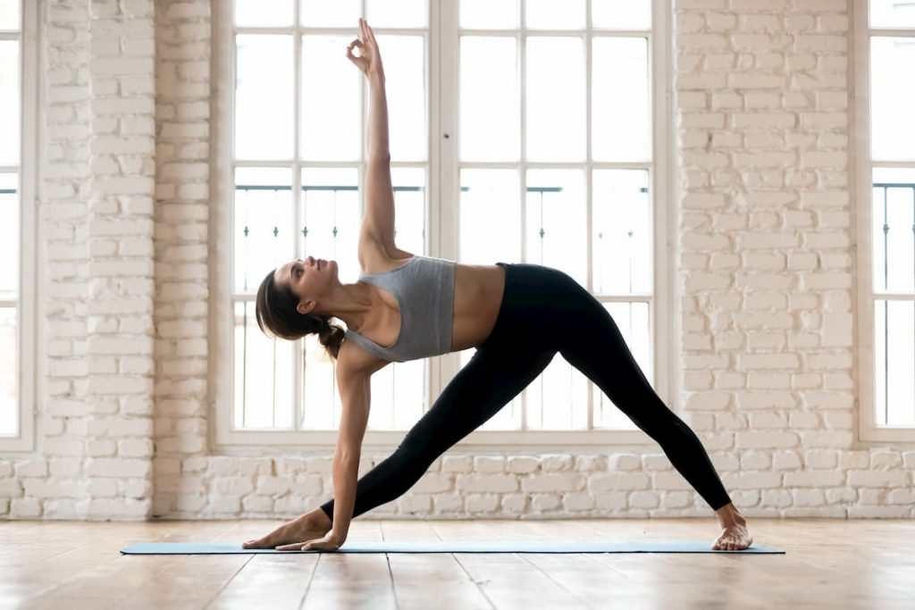 Young attractive yogi woman practicing yoga, doing Utthita Trikonasana exercise, extended triangle pose, working out, wearing sportswear, black pants and top, indoor full length, white yoga studio