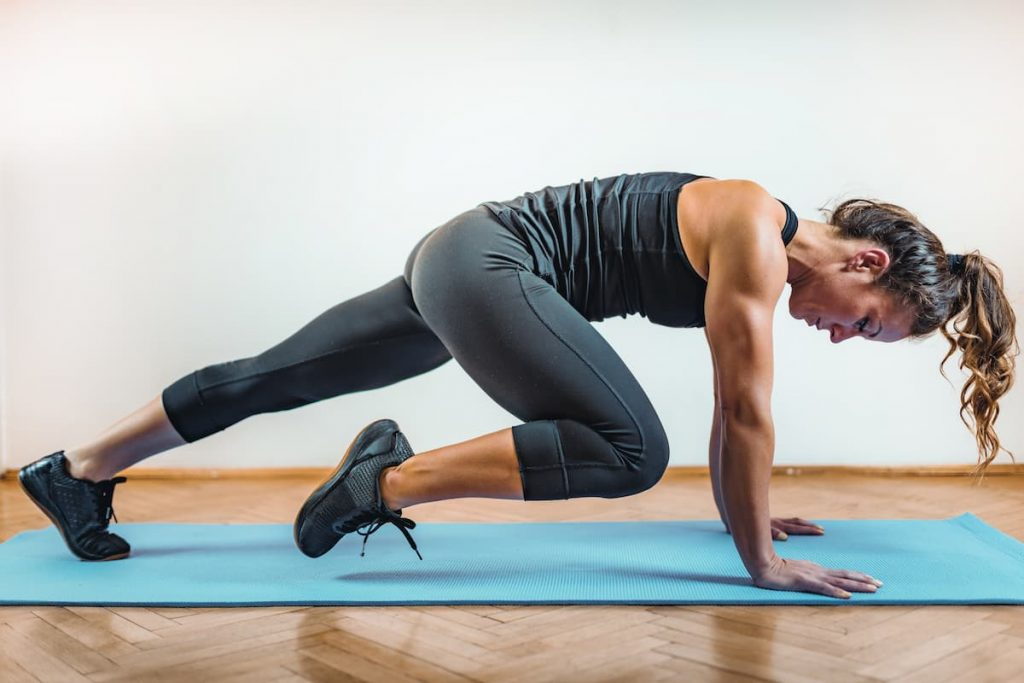Lady doing knees tucks High Intensity Interval Training on an Indoors mat