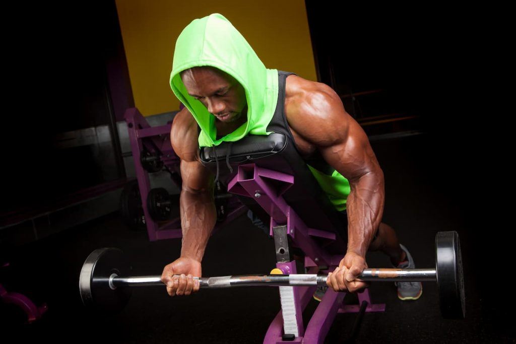 Man in a gym who is toned and ripped with lean muscle who is lifting weights using a curl bar on an angled bench