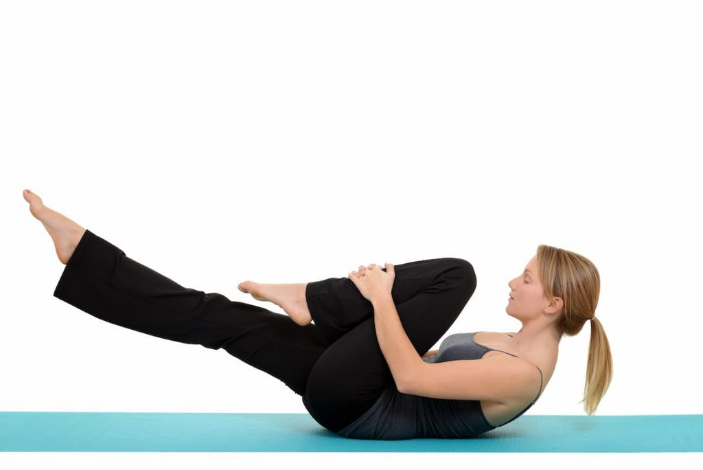 Woman doing Pilates single leg stretch one leg pulled to chest other leg lifted a foot off the ground and shoulders pulled up working the abs